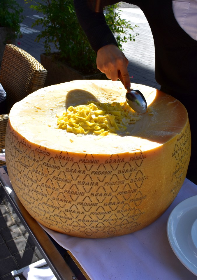 pasta in a wheel of cheese being tossed.