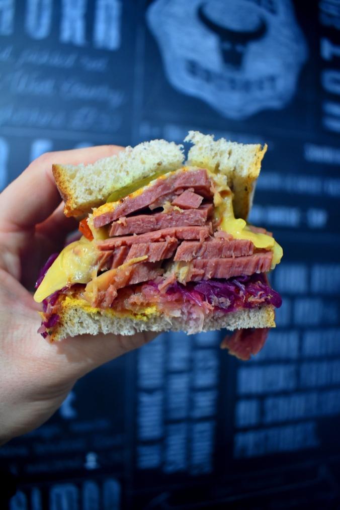 Sandwich with rye sourdough,Pink salt beef, sauerkraut and gherkins on a chalkboard backdrop