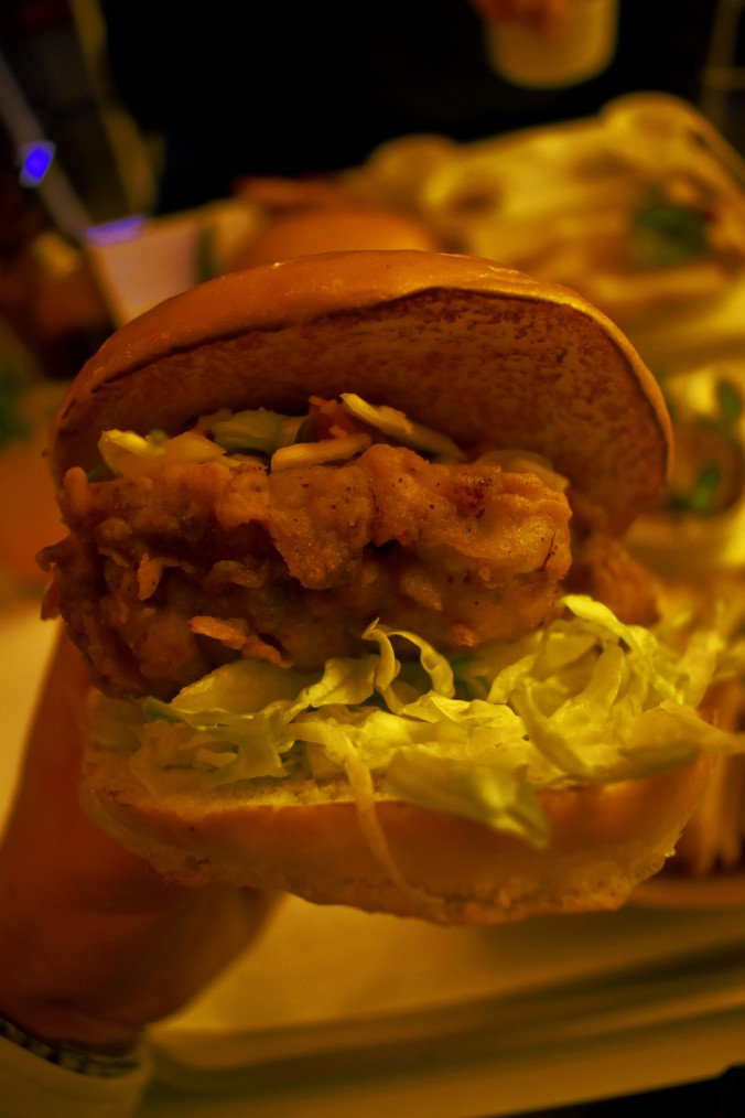 fried chicken burger in bun with salad