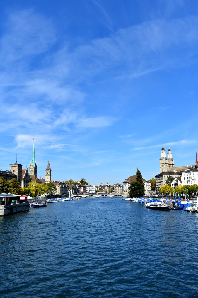 Zurich's river with boats and buildings along the banks. In the daytime.