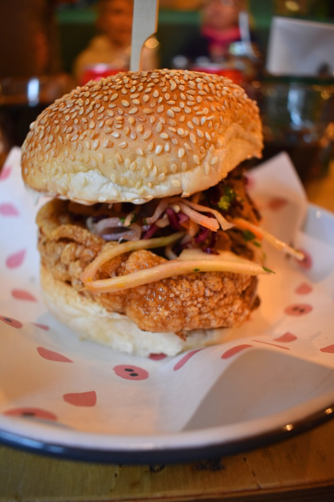Belly pork and coleslaw in a seeded bun on a table.