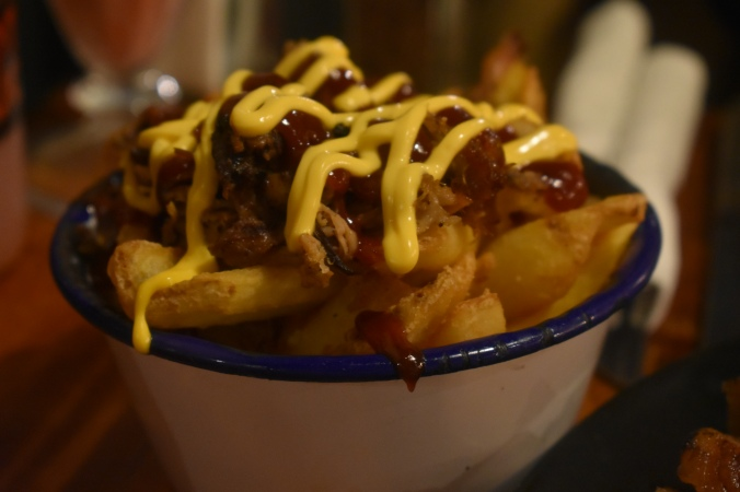 Fries covered in mustard and pulled pork in a white pot