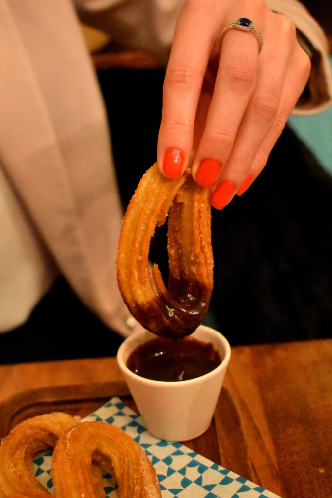 Churros hoop being dipped into a dark chocolate sauce