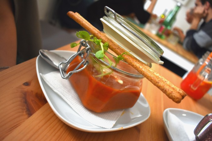tomato soup in a jar topped with breadsticks