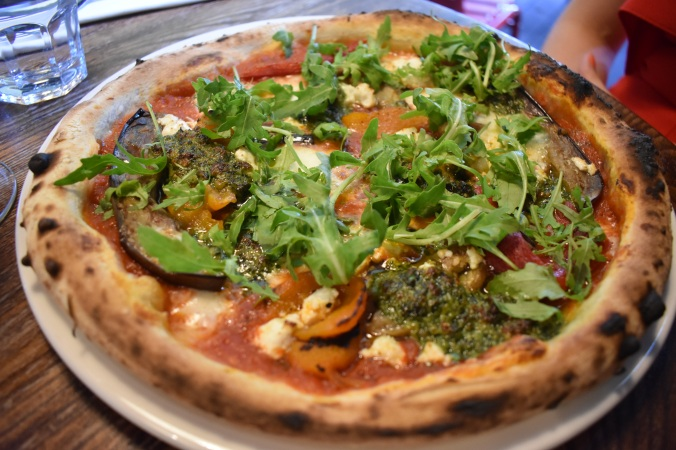 pizza topped with roasted vegetables and green pesto.